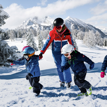 Kids running through the snow-covered landscape of Snow Space Salzburg ski resort together with their skiing instructor | © Armin Walcher, Skischule Alpendorf