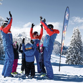 Four children and three skiing instructors having fun and throwing their hands up in the air, with the snow-covered landscape of Snow Space Salzburg ski resort in the background | © Armin Walcher, Skischule Alpendorf