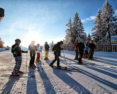 A group of skiers wait together at the mountain station Flachau on a sunny winter day
