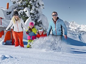 Laughing parents with two kids in the powder next to play elements on Ghost Mountain in St. Johann-Alpendorf at Snow Space Salzburg | © Alpendorf Bergbahnen AG