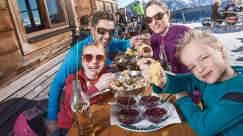 Family enjoying their Kaiserschmarrn with stewed plums on the sun terrace of a mountain hut at Snow Space Salzburg | © Flachau Tourismus  GmbH