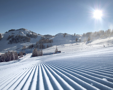 Freshly groomed slope in the sunshine of St. Johann-Alpendorf at Snow Space Salzburg ski resort, with a view of Sonntagskogel mountain | © Alpendorf Bergbahnen AG