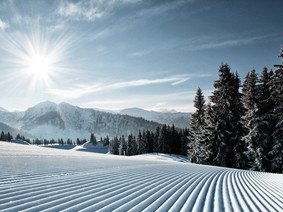 View to the just recently prepared slopes of the ski area St. Johann with sunshine