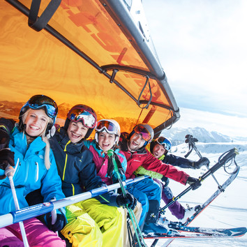 Shot of five friends on a chairlift, laughing and having fun during a ride up the mountain at Snow Space Salzburg | © Flachau Tourismus  GmbH