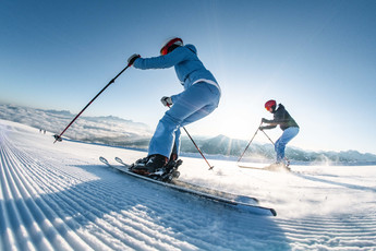 Skiers enjoy the good prepared slopes of the ski area Snow Space in Salzburg