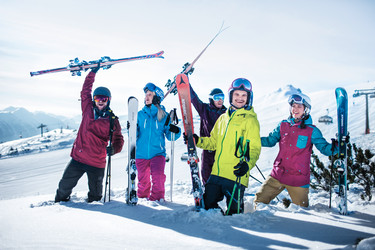 Group of laughing skiers holding their skis in the deep powder of Snow Space Salzburg ski resort | © Flachau Tourismus  GmbH