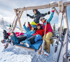 Skiers enjoy their break on the hollywood swing of the ski area Flachau with a lot of fun