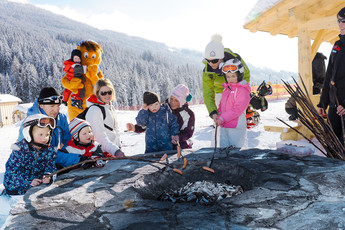 Kinder und Erwachsene halten Würstchen ins Feuer bei der Skizwergerl Grillparty in WAGRAINi's Winterwelt im Snow Space Salzburg | © Bergbahnen AG Wagrain