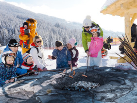 Children and adults cooking sausages over a fire during the ski bunnies barbecue party at WAGRAINi's Winter World at Snow Space Salzburg | © Bergbahnen AG Wagrain