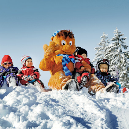 Children enjoy the skiing holiday in a playful manner with the mascot of the ski area of Wagrain