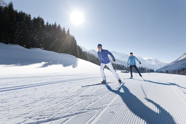 Two cross-country skiers leaving their tracks on a sunny cross-country skiing run in Wagrain at Snow Space Salzburg ski resort | © Wagrain-Kleinarl Tourismus /Salzburger Land Tourismus