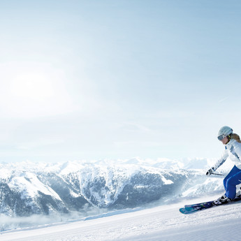 Key visual with skier and panoramic views of Flachau in the background