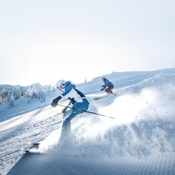 Two skiers leaving their turns on the perfectly groomed slopes of Snow Space Salzburg ski resort | © Ski amadé