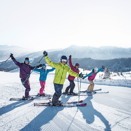 Five skiers with their hands up in the air, posing for the camera with the mountains of Snow Space Salzburg in the background | © Flachau Tourismus  GmbH