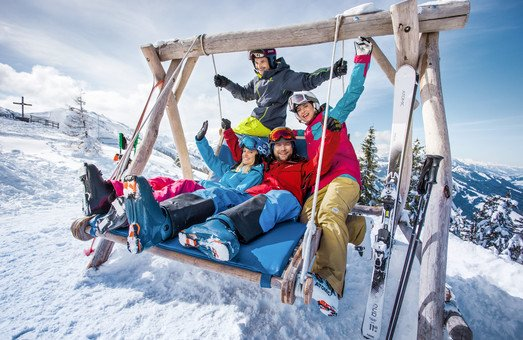 Five friends relaxing on a wooden swing in Flachau at Snow Space Salzburg ski resort | © Flachau Tourismus  GmbH
