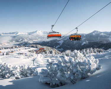 Starjet 3 chairlift in Flachau with snow-covered landscape and the mountains of the Salzburger Land province in the background | © Bergbahnen Flachau GmbH
