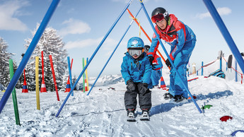 The little ones learn skiing from the professionals in the ski school Alpendorf in the children's land