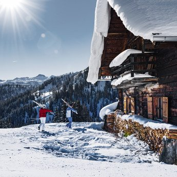 Two skiers shouldering their skis, about to take a break at a sunny mountain hut at Snow Space Salzburg ski resort | © Ski amadé